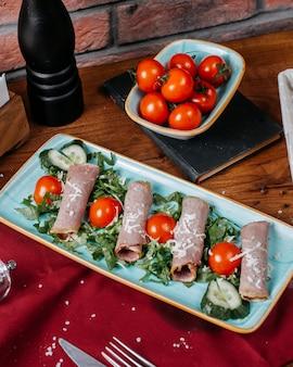 Vista lateral del rollo de jamón con tomates y pepinos en un plato