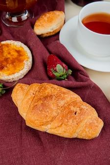 Vista lateral del rollo de media luna con crujiente de pan crujiente de fresa en tela bordo con una taza de té en la mesa blanca
