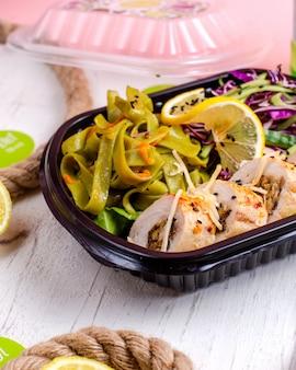 Vista lateral del rollo de pollo relleno con ajo vegetal y nueces servido con ensalada de repollo y rodaja de limón en la caja de entrega