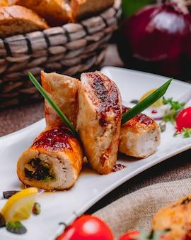 Vista lateral del rollo de pollo con verduras rellenas y una rodaja de limón