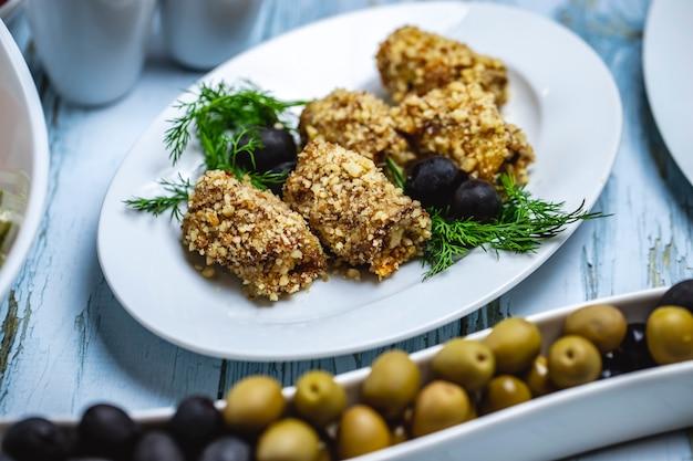 Vista lateral rollos de berenjena con nueces eneldo aceitunas negras y geen sobre la mesa