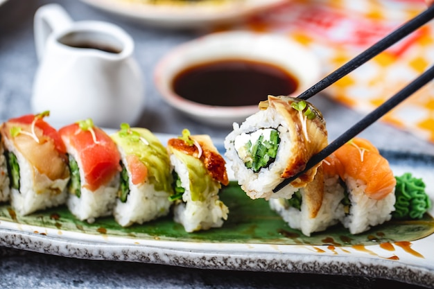 Vista lateral de los rollos de filadelfia con salmón aguacate cogner anguila pepino y salsa de soja sobre la mesa