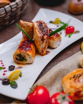 Vista lateral de rollos de pollo rellenos de nueces, ajo y hierbas en un plato