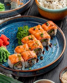 Vista lateral de rollos de sushi con anguila de salmón, aguacate y queso crema en un plato con jengibre y wasabi