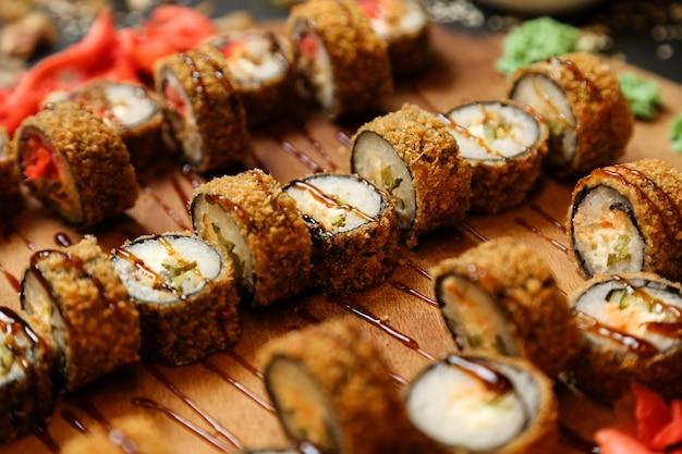 Vista lateral rollos de sushi fritos en una bandeja con jengibre y wasabi