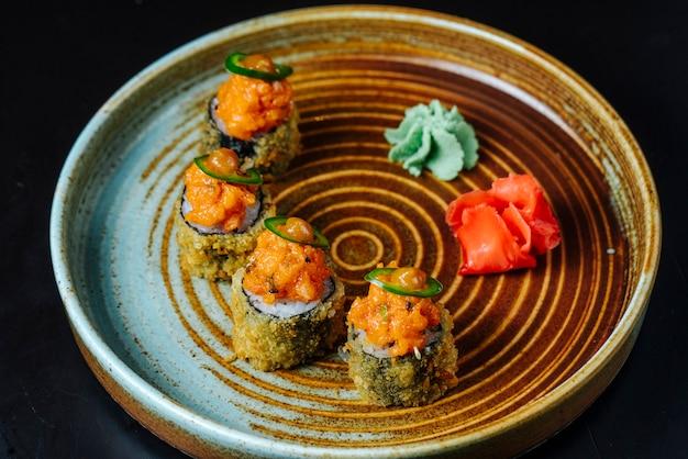 Vista lateral rollos de sushi fritos con salsa de wasabi y jengibre en un plato