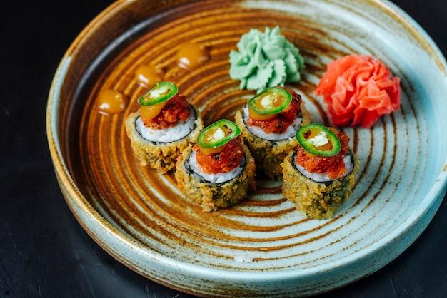 Vista lateral rollos de sushi fritos con wasabi y jengibre en un plato