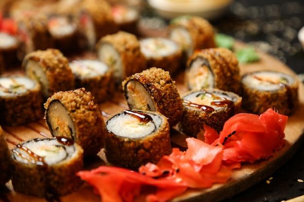 Vista lateral rollos de sushi fritos con wasabi y jengibre en un soporte
