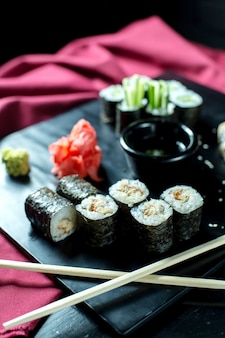 Vista lateral de rollos de sushi negro con anguila servido con jengibre y salsa de soja en pizarra