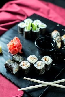 Vista lateral rollos de sushi negro con atún servido con jengibre y salsa de soja en pizarra