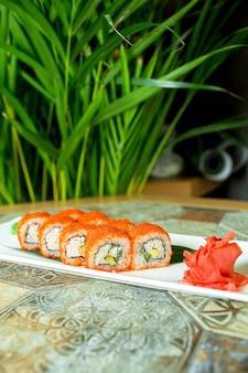 Vista lateral de rollos de sushi con queso crema de carne de cangrejo y aguacate en caviar de pez volador servido con rodajas de jengibre en verde