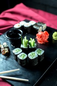 Vista lateral de rollos de sushi vegetariano negro con pepinos servidos con jengibre y salsa de soja en pizarra
