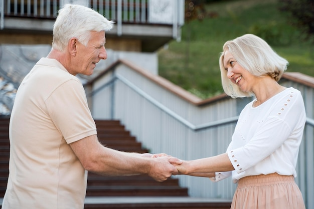 Vista lateral de la romántica y amorosa pareja senior cogidos de la mano al aire libre