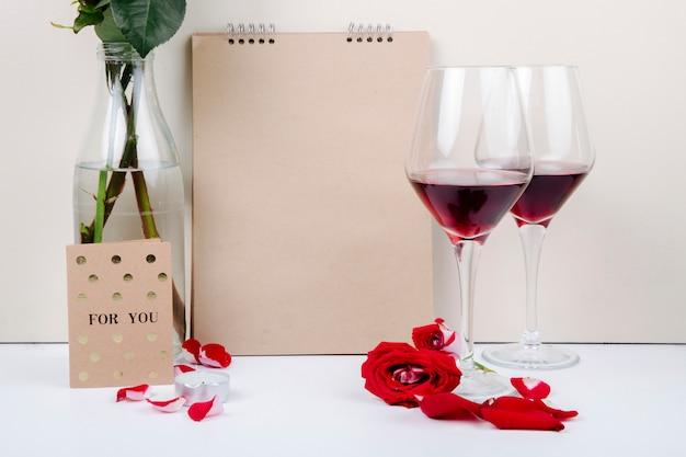 Vista lateral de rosas rojas en una botella de vidrio de pie cerca de un cuaderno de bocetos y dos copas de vino tinto sobre fondo blanco.