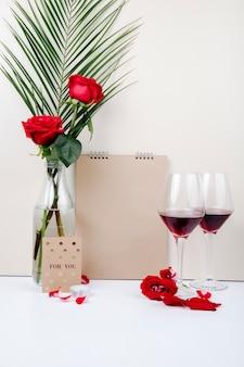 Vista lateral de rosas rojas con hoja de palma en una botella de vidrio de pie cerca de un cuaderno de bocetos y dos copas de vino tinto sobre fondo blanco.