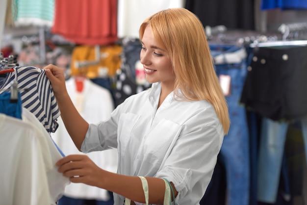 Vista lateral de la rubia en busca de ropa nueva en la tienda