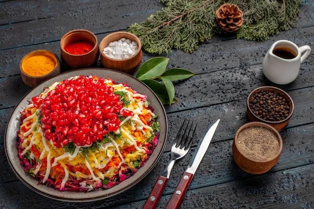 Vista lateral sabrosa comida apetitosa comida navideña y cuencos de aceite y especias junto a las ramas de abeto tenedor cuchillo con conos