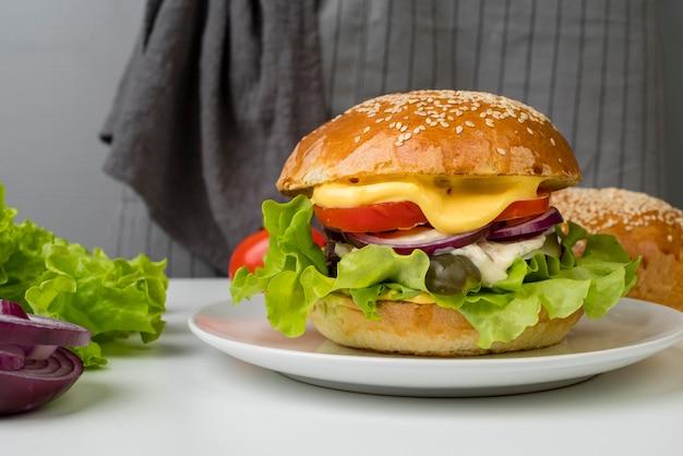 Vista lateral sabrosa hamburguesa con queso en mesa blanca