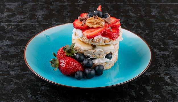 Vista lateral de sabroso pan crujiente con arándanos maduros, fresas y nueces con crema agria en un plato de cerámica en superficie rústica de madera