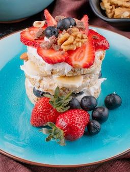 Vista lateral de sabroso pan crujiente con arándanos maduros, fresas y nueces con crema agria en un plato de cerámica