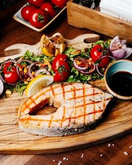 Vista lateral de salmón a la plancha con tomates frescos y hierbas de limón con salsa de narsharab sobre tabla de madera