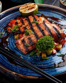 Vista lateral del salmón a la plancha con verduras, limón y salsa de soja en un plato sobre la mesa de madera
