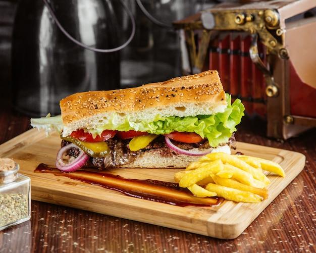 Vista lateral sandwich de carne con papas fritas en el tablero