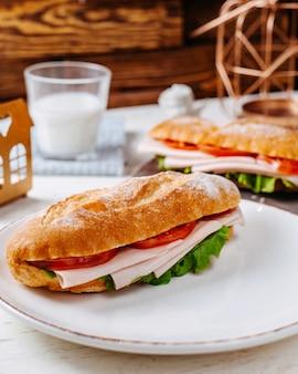 Vista lateral del sandwich con carne y tomate en placa