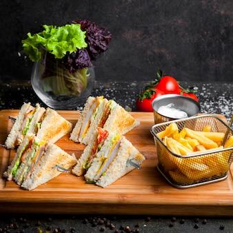 Vista lateral sándwich club con salsa de salsa de tomate y mayonesa y papas fritas en tabla de servir de madera