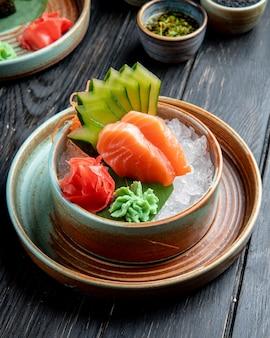 Vista lateral de sashimi de salmón con pepinos en rodajas de jengibre y salsa de wasabi en cubitos de hielo en un recipiente en la mesa de madera