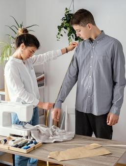 Vista lateral del sastre femenino midiendo la camisa de los clientes masculinos