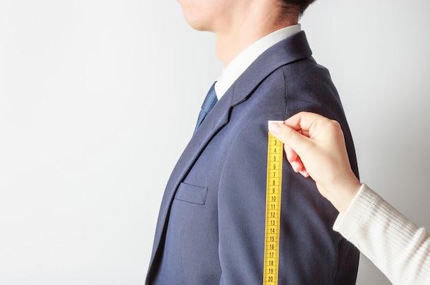 Vista lateral del sastre midiendo el traje de hombre