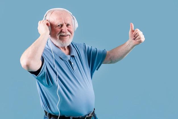Vista lateral senior mostrando signo ok para música