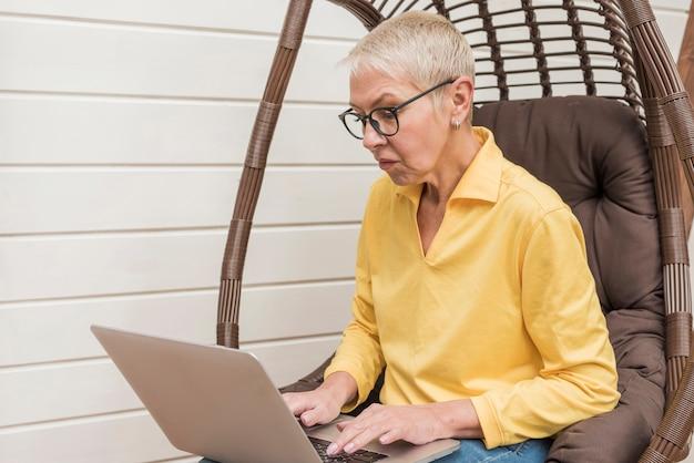Vista lateral senior mujer trabajando en su computadora portátil
