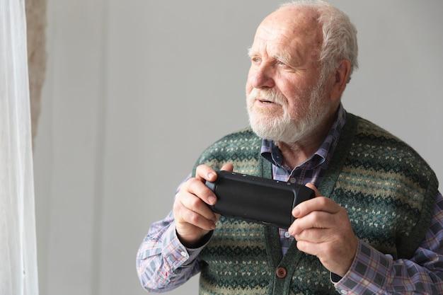 Vista lateral senior con teléfono y espacio de copia