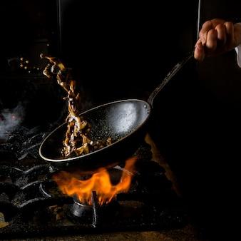 Vista lateral setas freír con estufa de gas y fuego y mano humana en sartén