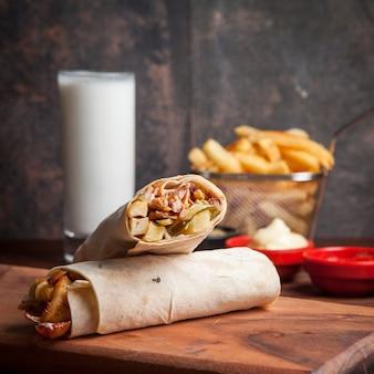 Vista lateral shawarma con papas fritas y ayran y mayonesa en utensilios de cocina