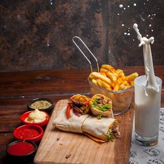 Vista lateral shawarma con papas fritas y ayran y salpicaduras en utensilios de cocina