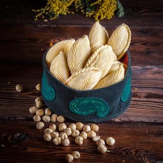 Vista lateral shekerbura con nueces y flores de mimosa en sombrero nacional en mesa de madera