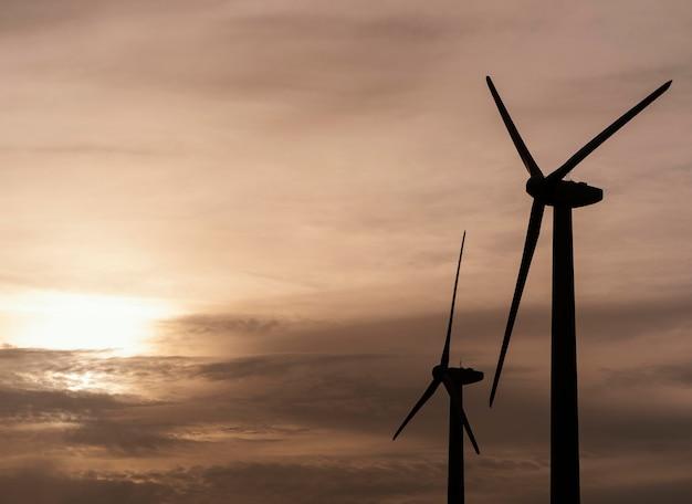 Vista lateral de la silueta de la turbina eólica generando electricidad