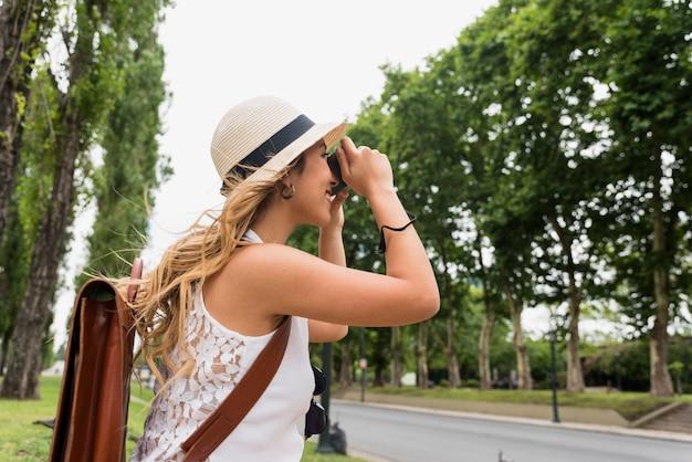 Vista lateral de un sombrero que lleva de la mujer rubia joven que toma la fotografía en cámara