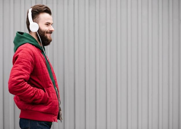 Vista lateral sonriente con barba y auriculares