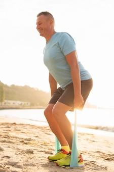 Vista lateral del sonriente hombre senior trabajando con cuerda elástica en la playa