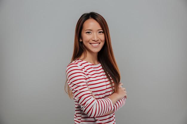 Vista lateral de la sonriente mujer asiática en suéter posando con los brazos cruzados y mirando a la cámara sobre fondo gris