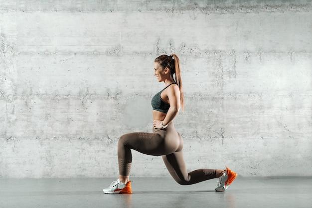 Vista lateral de la sonriente mujer caucásica deportiva vestida con ropa deportiva y con cola de caballo haciendo estocadas en el gimnasio.