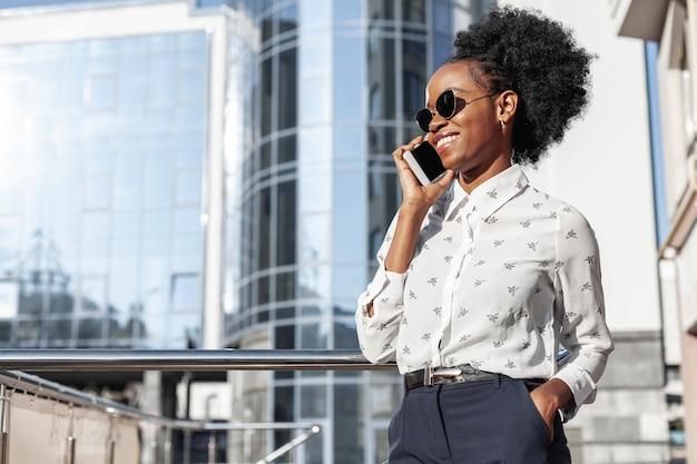 Vista lateral sonriente mujer hablando por teléfono