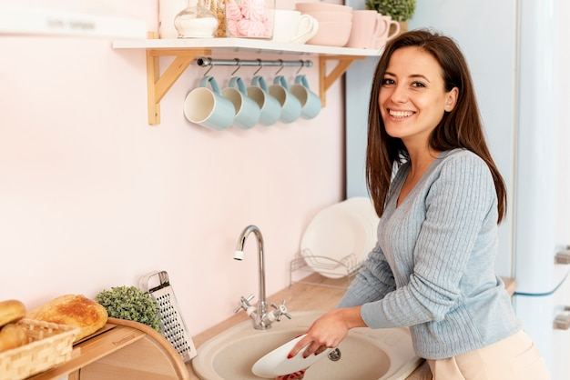 Vista lateral sonriente mujer lavando los platos