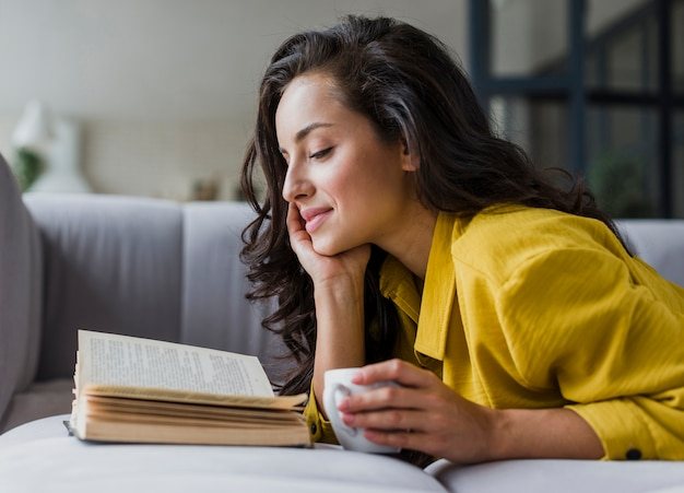 Vista lateral sonriente mujer leyendo libro