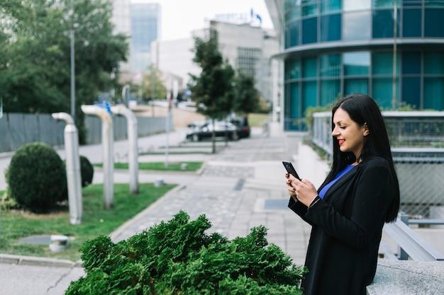 Vista lateral, de, un, sonriente, mujer de negocios, utilizar, teléfono móvil