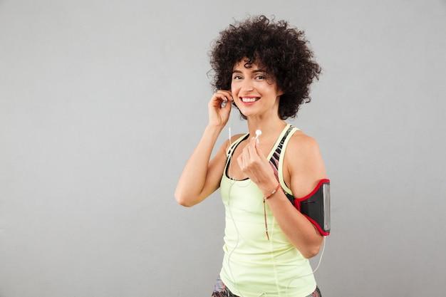 Vista lateral de sonriente mujer rizada fitness escuchando música